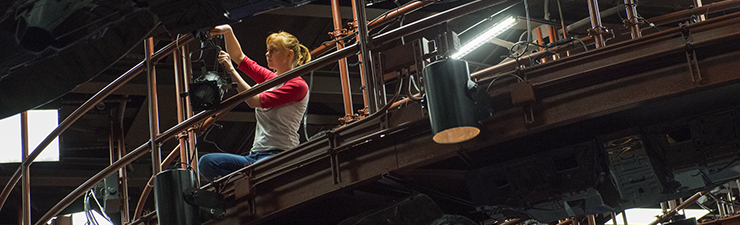 USI Theatre student hanging lights in the new theatre
