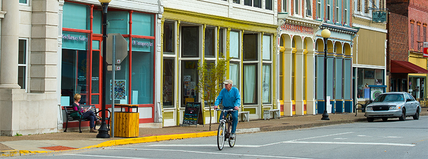 A bicyclist rides down main street in New Harmony