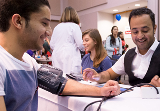 Student getting blood pressure checked at healthfair, smiling