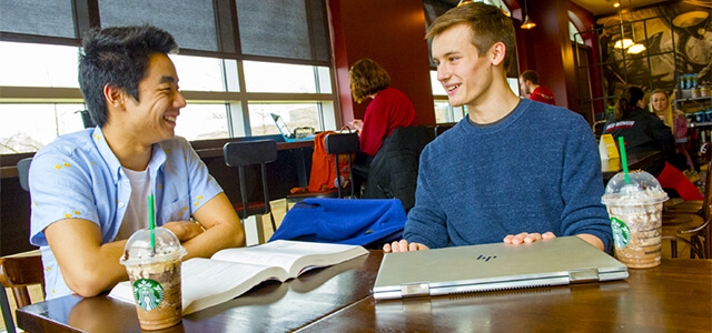 Two students, sitting at Starbucks, laughing while studying with Starbucks cups nearby