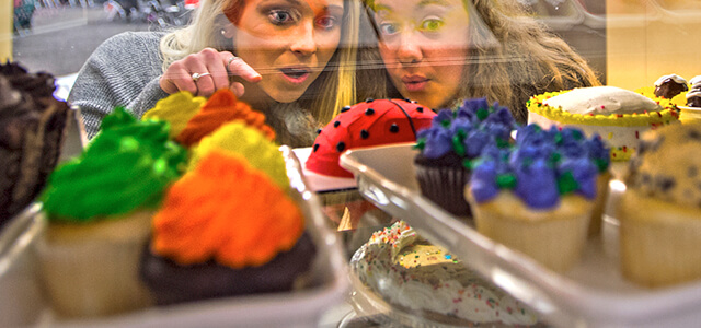 two students, looking into glass of baked treats, pointing
