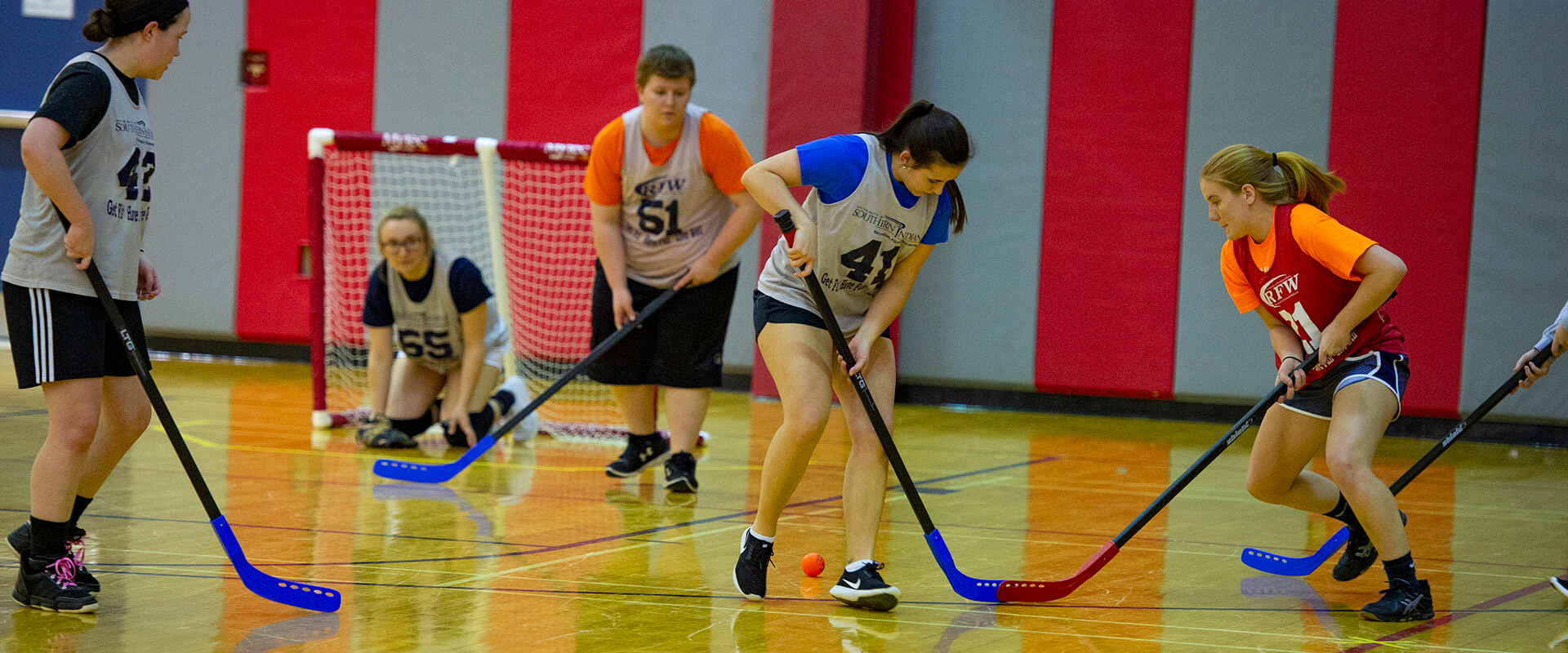 students playing hockey in gym
