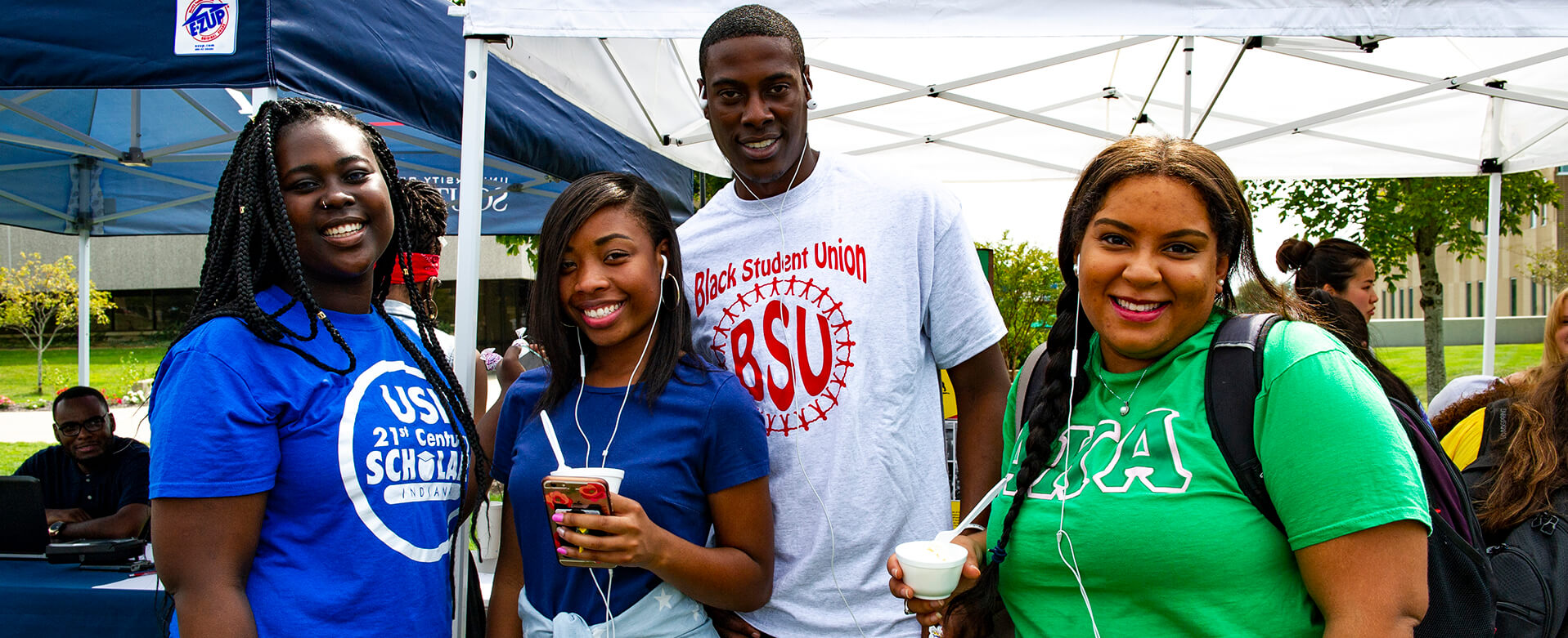 four students at involvement fair, enjoying ice-cream, wearing t-shirts that represent their various organizations (USI 21st century scholars, Black Student Union, sorority)