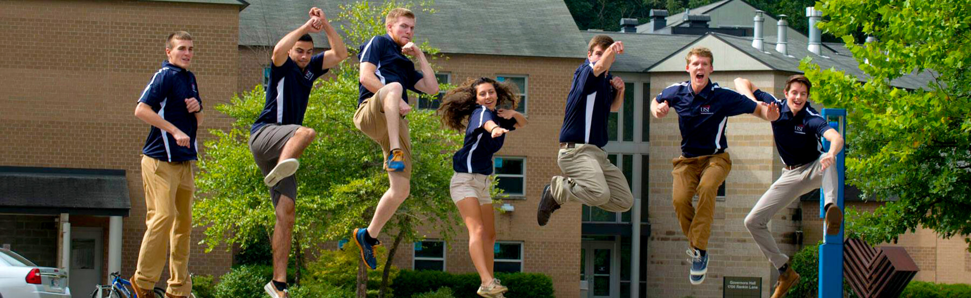 Evan and 6 other student ambassadors, jumping into the air happily