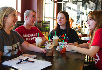 Students talk and laugh while sitting at Starbucks