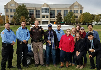 Public safety officers, sheriff, and students pose for picture in quad