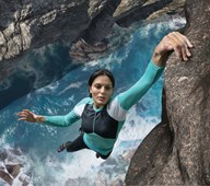 woman dangling from cliff with one hand, with intense ocean waves directly below her